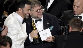 """Jimmy Kimmel, left, congratulates Guillermo del Toro in the audience after winning the award for best picture for """"The Shape of Water"""" at the Oscars on Sunday, March 4, 2018, at the Dolby Theatre in Los Angeles. (Photo by Chris Pizzello/Invision/AP)"""