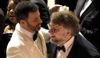 """Guillermo del Toro, right, winner of the award for best picture for """"The Shape of Water"""" celebrates with host, Jimmy Kimmel at the Oscars on Sunday, March 4, 2018, at the Dolby Theatre in Los Angeles. (Photo by Chris Pizzello/Invision/AP)"""