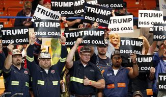 A group of coal miners wave Trump signs as they wait for a rally in Charleston, W.Va., Thursday, May 5, 2016.  (AP Photo/Steve Helber)
