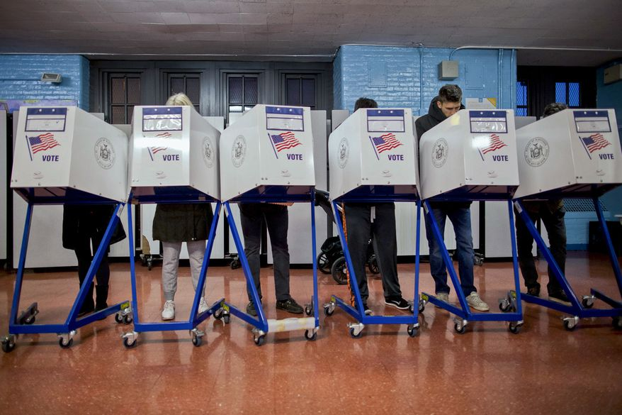 In this photo from Tuesday, Nov. 8, 2016, voters fill out their forms as they prepare to vote at a polling station in the Brooklyn borough of New York. Data from the N.Y. State Board of Elections show there are 18,000 active GOP voters on the rolls as of Nov. 2019 than there were on the eve of President Trump's election in Nov. 2016. (AP Photo/Alexander F. Yuan, File) **FILE**