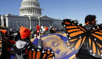 """Wearing """"butterfly wings,"""" supporters of the Deferred Action for Childhood Arrivals (DACA) program hold a tarp with an image of President Donald Trump as they march in support of DACA, Monday, March 5, 2018, on Capitol Hill in Washington. (AP Photo/Jacquelyn Martin)"""