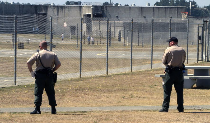 In this Aug. 17, 2011 file photo, correctional officers keep watch on inmates in the recreation yard at Pelican Bay State Prison near Crescent City, Calif. (AP Photo/Rich Pedroncelli, File) **FILE**