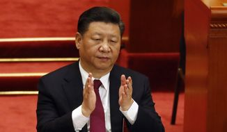 Chinese President Xi Jinping applauds during the opening session of the annual National People's Congress in Beijing's Great Hall of the People, Monday, March 5, 2018. (AP Photo/Ng Han Guan)