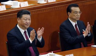 Chinese President Xi Jinping, left, and Chinese Premier Li Keqiang applaud during the opening session of the annual National People's Congress at the Great Hall of the People in Beijing, Monday, March 5, 2018. (AP Photo/Andy Wong)