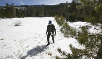 FILE - In this Feb. 1, 2018 file photo, Frank Gehrke, chief of the California Cooperative Snow Surveys Program for the Department of Water Resources, leaves a snow covered meadow after conducting the second snow survey of the season near Echo Summit, Calif. Welcome drifts of fresh snow await California's water managers on their late-winter survey of the Sierra Nevada snowpack. California water officials were trooping into the mountains Monday, March 5, for the latest in their regular manual measurements of the year's snowfall. (AP Photo/Rich Pedroncelli, File)