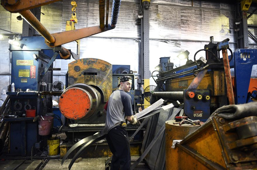 In this Feb. 20, 2018, photo, slitter operator Dylan McCone of Philadelphia works inside Camden Yards Steel in Camden, N.J. The company makes an effort to hire workers from within the city, offering job training and sometimes even a trip to the bank to help open a checking account. (Joe Lamberti/Camden Courier-Post via AP)