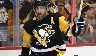 Pittsburgh Penguins' Kris Letang celebrates his goal in the second period of an NHL hockey game against the Calgary Flames in Pittsburgh, Monday, March 5, 2018. (AP Photo/Gene J. Puskar)
