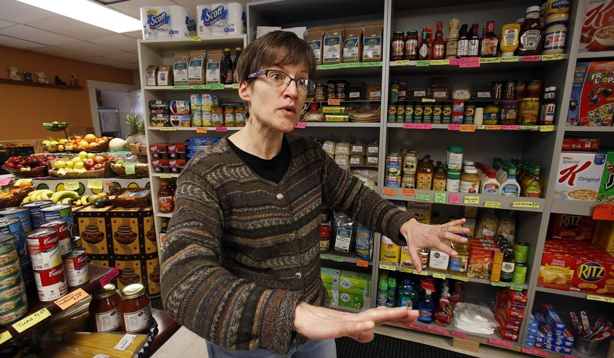 """In this Feb. 26, 2018 photo, Dianne Shenk talks to a customer in her Dylamatos Market in Hazelwood, Pa. About a quarter of Shenk's customers pay with benefits from the federal Supplemental Nutrition Assistance Program, so the government's proposal to replace the debit card-type program with a pre-assembled box of shelf-stable goods delivered to recipients concerns her and other grocery operators in poor areas. """"These boxes will be full of shelf-stable items, the same things we're being told not to eat,"""" she said. (AP Photo/Gene J. Puskar)"""