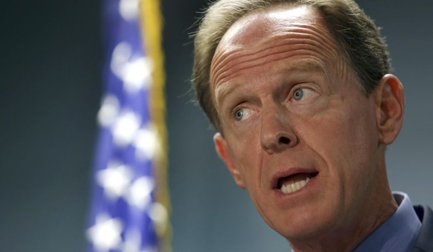 U. S. Sen. Pat Toomey, R-Pa., speaks during a press conference with U.S, Sen. Chris Coons, D-Del., Monday, March 5, 2018, in Philadelphia. Toomey and Coons say they'll introduce a bill Monday that will require federal authorities to notify states when a felon or a fugitive attempts to buy a firearm but fails the National Instant Criminal Background Check System. (AP Photo/Jacqueline Larma)
