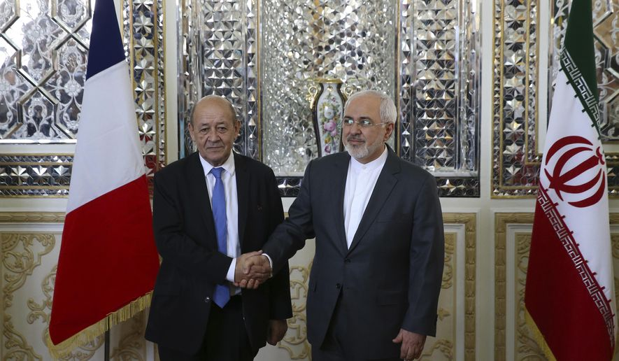 Iranian Foreign Minister Mohammad Javad Zarif, right, and his French counterpart Jean-Yves Le Drian, shake hands for journalists at the start of their meeting in Tehran, Iran, Monday, March 5, 2018. Le Drian arrived in Tehran amid French criticism of Tehran's ballistic missile program. His one-day trip highlights the balancing act Paris finds itself in after Iran's 2015 nuclear deal with world powers. (AP Photo/Vahid Salemi)