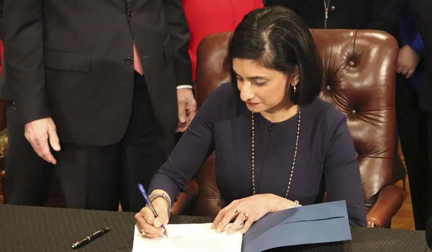 In this file photo, Seema Verma, the head of the Centers for Medicare and Medicaid Services, signs paperwork at the state Capitol in Little Rock, Ark., on Monday, March 5, 2018, that gives the state permission to require that thousands of people on its Medicaid expansion seek ways to work or volunteer. In March 2018, Ms. Verma rejected the state of Idaho's proposals for a workaround of Obamacare regulations. (AP Photo/Kelly P. Kissel)