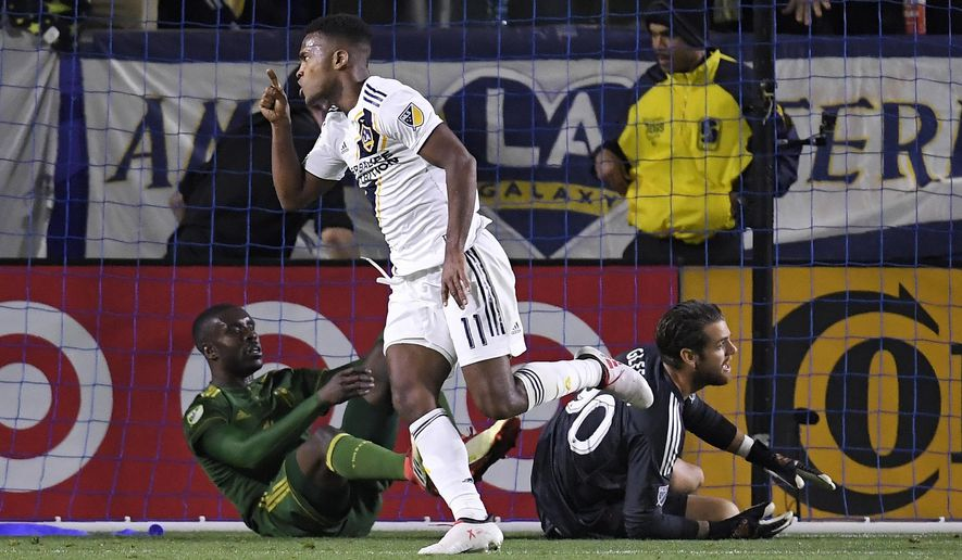 Los Angeles Galaxy forward Ola Kamara, center, celebrates his goal as Portland Timbers defender Larrys Mabiala, left, and goalkeeper Jake Gleeson lie on the ground during the first half of a Major League Soccer game, Sunday, March 4, 2018, in Carson, Calif. (AP Photo/Mark J. Terrill)