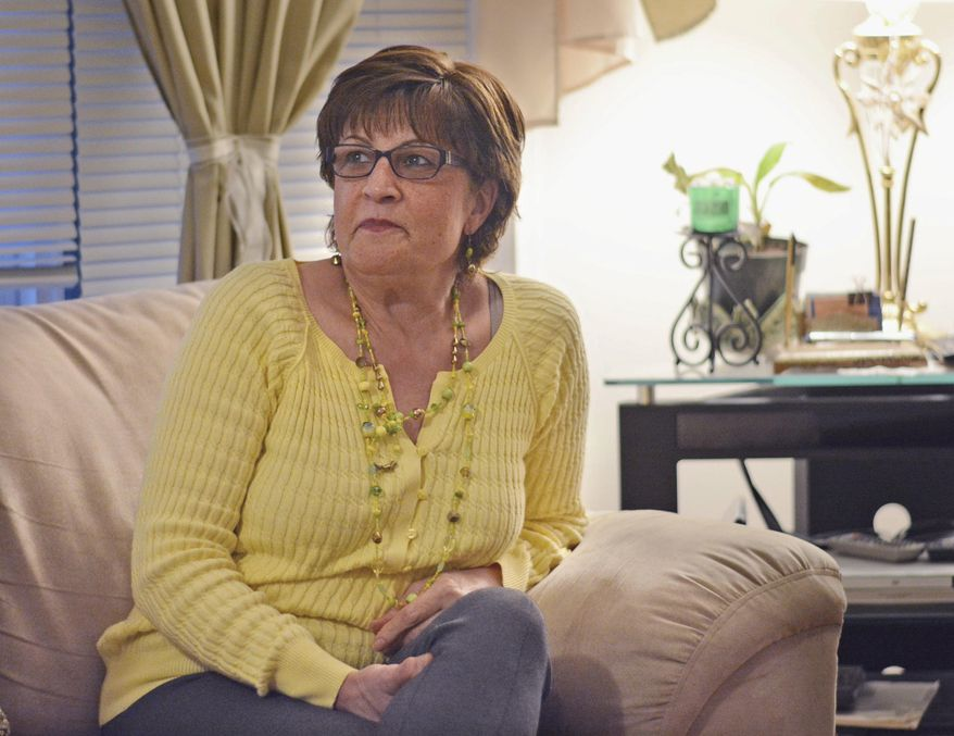 In a Feb. 15, 2018 photo, Fahimeh Alavi sits in her Anacortes, Wash. home and recounts the perilous journey she and her small daughters took to flee Iran's revolutionary government in the mid 1980s.  (Charles Biles/Skagit Valley Herald via AP)