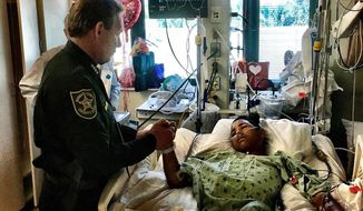 This image made available by the Broward County Sheriff's Office on Sunday, Feb. 18, 2018, shows Sheriff Scott Israel, holding the hand of Anthony Borges, 15, a student at Marjory Stoneman Douglas High School. The teenager was shot five times during the massacre on Valentine's Day that killed 17 students. Borges is being credited with saving the lives of at least 20 other students. (Broward County Sheriff's Office via AP)