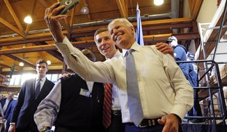 Conor Lamb, center, the Democratic candidate for the March 13 special election in Pennsylvania's 18th Congressional District, and former Vice President Joe Biden, right, pose for a selfie with a supporter during a rally at the Carpenter's Training Center in Collier, Pa., Tuesday, March 6, 2018. (AP Photo/Gene J. Puskar)
