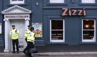 "Police outside an Italian restaurant in Salisbury, England, Tuesday March 6, 2018, near to where former Russian spy double agent Sergei Skripal and his companion were found critically ill Sunday following exposure to an ""unknown substance."" The 66-year old Skripal and an unidentified woman companion are being treated in hospital after they were found unconscious on the park bench in Salisbury. (Steve Parsons/PA via AP)"