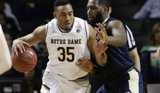 Pittsburgh's Jared Wilson-Frame (0) defends as Notre Dame's Bonzie Colson (35) works the ball during the first half of an NCAA college basketball game in the first round of the Atlantic Coast Conference tournament Tuesday, March 6, 2018, in New York. (AP Photo/Frank Franklin II)