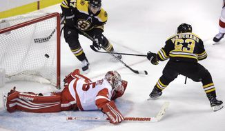 Boston Bruins left wing Brad Marchand (63) flicks a backhand shot over Detroit Red Wings goaltender Jimmy Howard (35) for the game-winning goal during the overtime period of an NHL hockey game in Boston, Tuesday, March 6, 2018. Marchand notched a hat trick in the Bruins' 6-5 win. (AP Photo/Charles Krupa)