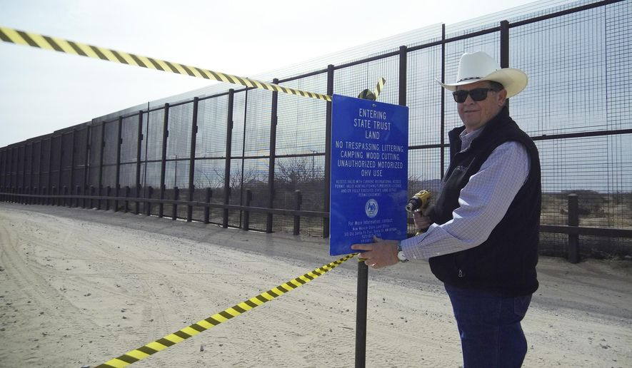 This photo provided by the New Mexico State Land Office shows New Mexico Land Commissioner Aubrey Dunn installing a sign along the U.S.-Mexico border to indicate the land belongs to the state Tuesday, March 6, 2018, near Santa Teresa, N.M. New Mexico's top land manager posted signs along the U.S.-Mexico border aimed at blocking border patrol operations on a one-mile stretch of state trust land over concerns that the federal government is not compensating the state for using the land. (Kris McNeil/New Mexico State Land Office via AP)
