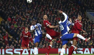 Liverpool's Dejan Lovren, center, attempts a header at goal during the Champions League round of 16, second leg, soccer match between Liverpool and FC Porto at Anfield Stadium, Liverpool, England, Tuesday March 6, 2018. (AP Photo/Dave Thompson)