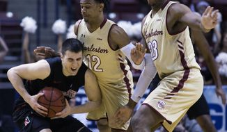 College of Charleston's Cameron Johnson, center and Nick Harris, at right, guards Northeastern's Vasa Pusica, at left, during the first half of an NCAA college championship basketball game in the Colonial Athletic Association tournament at the North Charleston Coliseum in North Charleston, S.C., Tuesday, March 6, 2018. (AP Photo/Mic Smith)