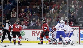 A shot by New Jersey Devils center Travis Zajac (19) enters the net of Montreal Canadiens goaltender Charlie Lindgren (39) during the first period of an NHL hockey game, Tuesday, March 6, 2018, in Newark, N.J. (AP Photo/Julio Cortez)