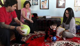 In this Feb. 16, 2018, photo, parents KP, left, and Zipora Niowong talk with nurse Michelle Thao about their 19-month-old son Zeph at their St. Paul, Minn. home. The Niowongs participate in the Ramsey County's Healthy Families program, which provides home visits from a nurse from pregnancy until a child is 3 years old. (Christopher Magan/Pioneer Press via AP)
