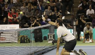 Roger Federer, of Switzerland, hits from his knees as he plays in an exhibition tennis match with partner Bill Gates against Jack Sock and Savannah Guthrie in San Jose, Calif., Monday, March 5, 2018. (AP Photo/Jeff Chiu)