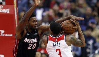 Miami Heat forward Justise Winslow (20) attempts to block a shot by Washington Wizards guard Bradley Beal (3) during the first half of an NBA basketball game Tuesday, March 6, 2018, in Washington. (AP Photo/Alex Brandon)