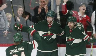 Minnesota Wild's Eric Staal, center, is congratulated by Michael Granlund, left, and Jason Zucker after Staal's power-play goal off Carolina Hurricanes goaltender Cam Ward during the first period of an NHL hockey game Tuesday, March 6, 2018, in St. Paul, Minn. (AP Photo/Jim Mone)