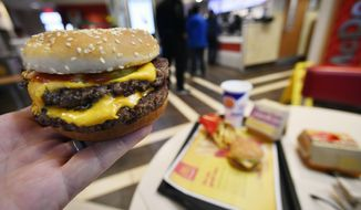 A McDonald's Double Quarter Pounder is shown with the new fresh beef Tuesday, March 6, 2018, in Atlanta. McDonald's is offering fresh beef rather than frozen patties in some burgers at thousands of restaurants, a switch it first announced about a year ago as it works to appeal to customers who want fresher foods. (AP Photo/Mike Stewart)