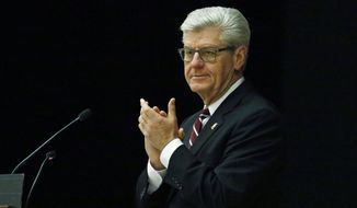 Mississippi Gov.Phil Bryant, a former lawman, applauds as he delivers remarks during Mississippi Highway Safety Patrol commencement exercises in Pearl, Miss., Tuesday, March 6, 2018. Fifty seven cadets were sworn in as troopers. (AP Photo/Rogelio V. Solis)