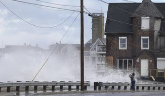A woman takes pictures of the high surf, Tuesday, March 6, 2018, as waves continue to breach the seawall in Marshfield, Mass. Utilities are racing to restore power to tens of thousands of customers in the Northeast still without electricity after last week's storm as another nor'easter threatens the hard-hit area with heavy, wet snow, high winds, and more outages. (AP Photo/Elise Amendola)