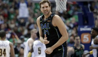 Dallas Mavericks center Dirk Nowitzki celebrates sinking a 3-point basket during the first half of the team's NBA basketball game against the Denver Nuggets in Dallas, Tuesday, March 6, 2018. (AP Photo/Tony Gutierrez)