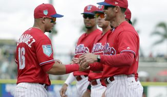 FILE - In this Feb. 24, 2018, file photo, Philadelphia Phillies manager Gabe Kapler, right, shakes hands with second baseman Cesar Hernandez (16) before a baseball spring exhibition game against the Baltimore Orioles in Clearwater, Fla. Kapler has brought a new-school philosophy, a ton of energy and plenty of positivity to an organization that needed revitalization after five straight losing seasons. (AP Photo/Lynne Sladky, File)