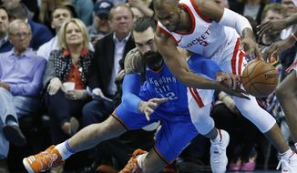 Oklahoma City Thunder center Steven Adams, left, reaches to in to knock the ball away from Houston Rockets guard Chris Paul, right, in the first half of an NBA basketball game in Oklahoma City, Tuesday, March 6, 2018. (AP Photo/Sue Ogrocki)