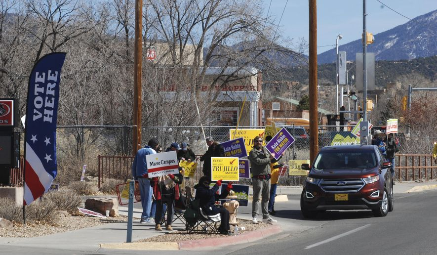 Campaign supporters for mayoral candidates in Santa Fe, N.M., crowd the sidewalks outside polls at Gonzales Community School on Tuesday, March 6, 2018. Residents of New Mexico's state capital city are picking a new mayor who will wield greater powers and earn an increased six-figure salary from a field of five candidates with no incumbent. (AP Photo/Morgan Lee)