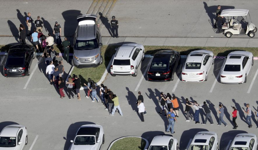 In this Feb. 14, 2018, file photo, students are evacuated by police from Marjory Stoneman Douglas High School in Parkland, Fla., after a shooter opened fire on the campus. (Mike Stocker/South Florida Sun-Sentinel via AP, File)