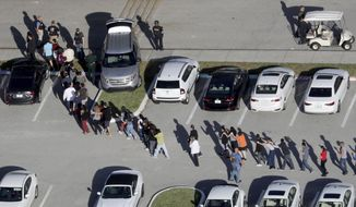 FILE - In this Feb. 14, 2018, file photo, students are evacuated by police from Marjory Stoneman Douglas High School in Parkland, Fla., after a shooter opened fire on the campus. Modern technology has enabled real-time reaction, support and calls for action during deadly mass shootings in the U.S. Live video of the Florida shooting showed survivors under desks while others live-tweeted messages to the survivors. (Mike Stocker/South Florida Sun-Sentinel via AP, File)