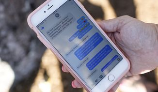 FILE - In this Feb. 15, 2018, file photo, Alana Koer, of Parkland, Fla., shows text messages she received from her son the day before, during a community vigil at Pine Trails Park in Parkland, Fla., for the victims of the shooting at Marjory Stoneman Douglas High School. Koer's son Kai Koer, survived the attack by Nikolas Cruz, a former student who was charged with 17 counts of premeditated murder. Modern technology has enabled real-time reaction, support and calls for action during deadly mass shootings in the U.S. Live video of the Florida shooting showed survivors under desks while others live-tweeted messages to the survivors. (AP Photo/Brynn Anderson, File)
