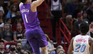 Phoenix Suns' Devin Booker (1) shoots over Miami Heat's Justise Winslow (20) during the second half of an NBA basketball game, Monday, March 5, 2018, in Miami. (AP Photo/Lynne Sladky)