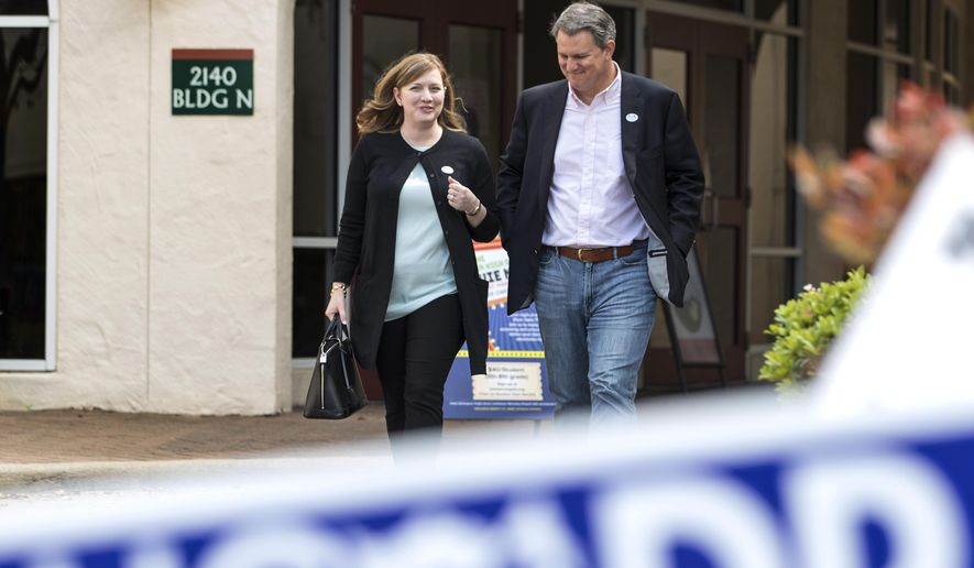 Lizzie Pannill Fletcher, a Democrat running for the 7th Congressional District seat in the U.S. House of Representatives, and her husband, Scott Fletcher, walk out of the polling place at St. Anne's Catholic Church after voting in the primary election on Tuesday, March 6, 2018, in Houston.  (Brett Coomer/Houston Chronicle via AP)