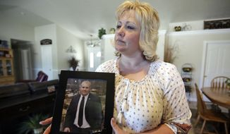 In this July 13, 2016, file photo, Laurie Holt holds a photograph of her son Joshua Holt at her home, in Riverton, Utah. A secret backchannel has opened up in 2018, between normally hostile Venezuelan and U.S. officials to discuss the possible release of Joshua Holt, jailed for more than 20 months in the volatile South American nation, multiple congressional sources have told the AP. (AP Photo/Rick Bowmer, File)