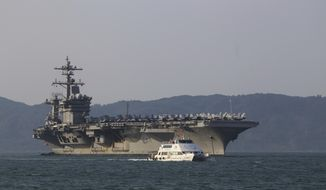 A Vietnamese passenger boat sails past U.S aircraft carrier USS Carl Vinson as it docks in Danang bay, Vietnam on Monday, March 5, 2018. For the first time since the Vietnam War, a U.S. Navy aircraft carrier is paying a visit to a Vietnamese port, seeking to bolster both countries' efforts to stem expansionism by China in the South China Sea. (AP Photo/ Hau Dinh)