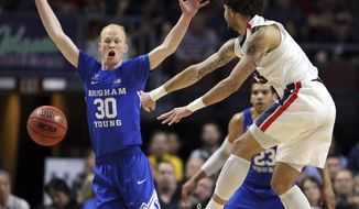 Gonzaga's Josh Perkins passes under BYU's TJ Haws (30) during the first half of the West Coast Conference tournament championship NCAA college basketball game Tuesday, March 6, 2018, in Las Vegas. (AP Photo/Isaac Brekken)