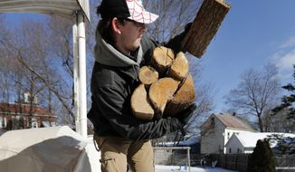 Corbin Chamberlain, 16, loads up on firewood to carry indoors, Saturday, Feb. 3, 2018, in Mechanic Falls, Maine. One firewood dealer says the average wait time for delivery of kiln-dried wood in the winter is usually about two weeks, but this year it's seven weeks. Experts say thousands of Maine residents were caught off guard by a warm fall that caused firewood customers to delay getting in their winter supplies. (AP Photo/Robert F. Bukaty)