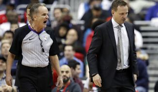 Referee Mike Callahan, left, talks to Washington Wizards head coach Scott Brooks during the first half of an NBA basketball game against the Indiana Pacers, Sunday, March 4, 2018, in Washington. (AP Photo/Alex Brandon)