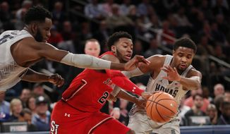 Georgetown's Jessie Govan, left, and Trey Dickerson, right, try to strip the ball from St. John's guard Shamorie Ponds, center, during the second half of an NCAA college basketball game in the first round of the Big East conference tournament, Wednesday, March 7, 2018, in New York. Ponds was the high scorer as St. Johns defeated Georgetown 88-77. (AP Photo/Kathy Willens)