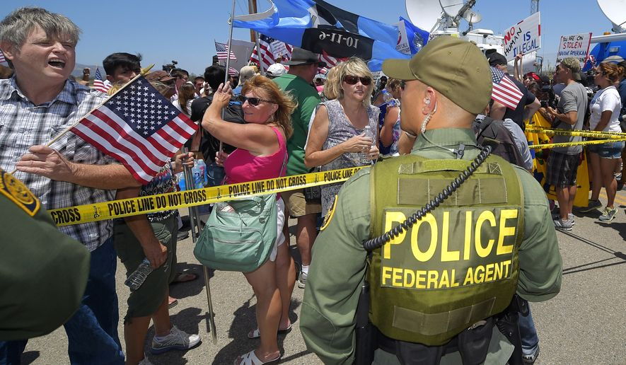 Demonstrators yell to a U.S. Customs and Border Protection officer, Friday, July 4, 2014, outside a U.S. Border Patrol station in Murrieta, Calif. Demonstrators on both sides of the immigration debate had gathered where the agency was foiled earlier this week in an attempt to bus in and process some of the immigrants who have flooded the Texas border with Mexico. (AP Photo/Mark J. Terrill)