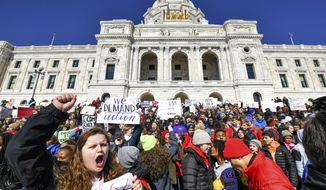 Thousands of high school students hold a rally after they walked out of their schools and marched to the state Capitol in Saint Paul, Minn., Wednesday, March 7, 2018, to protest gun violence and pressure lawmakers to enact stricter gun control. (Glen Stubbe/Star Tribune via AP)